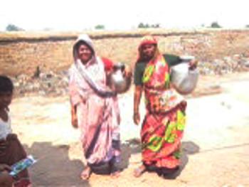 ইটভাটা থেকে জল নিয়ে ফিরছে নয়াবস্তির মেয়েরা। ছবি জিতেন নন্দীর তোলা।