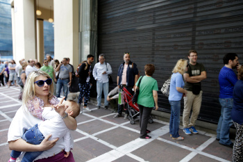People stand in a queue outside a bank which operates on Saturday but eventually didn't open, in central Athens, June 27, 2015. Greece's fraught bailout talks with its creditors took a dramatic turn early Saturday, with the radical left government announcing a referendum in just over a week on the latest proposed deal — and urging voters to reject it. (AP Photo/Thanassis Stavrakis)