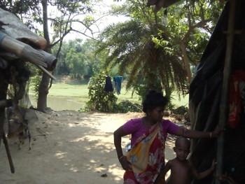 উঁচু রাস্তার একপাশে ঘর। ঘরের আরেক দিকে জলধারা। খালের ধারে খাসজমিতে ঘর। ছবি শমীক সরকারের তোলা। ৭ মে ২০১৬।